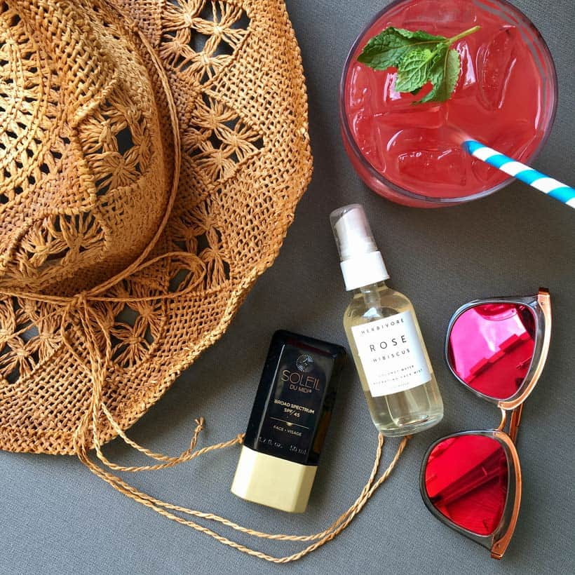 Soleil Toujours sunscreen flatlay photo of pool essentials sunglasses cocktail straw hat