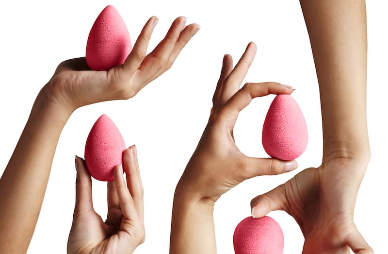 women holding pink beauty blender makeup sponges