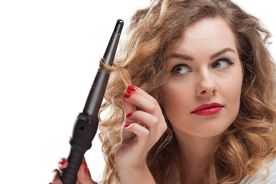 Woman curling her hair with a curling wand