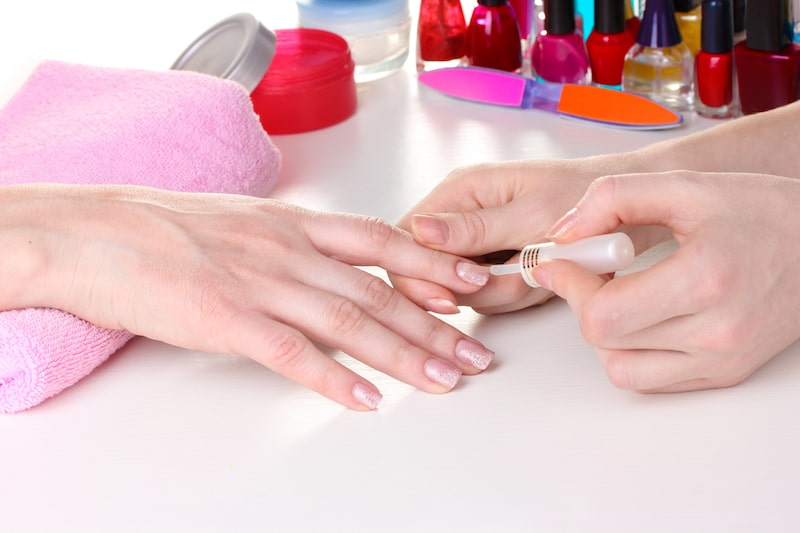 A woman getting a gel nail manicure with beautiful pink gel nail designs