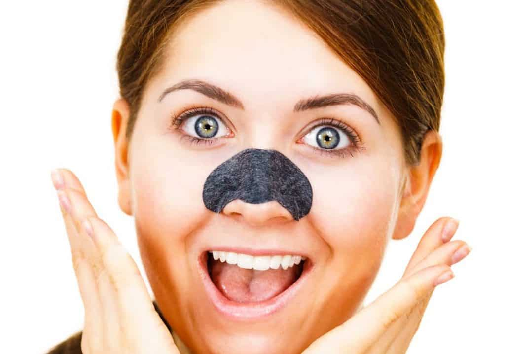 woman with blackhead removal strip on her nose