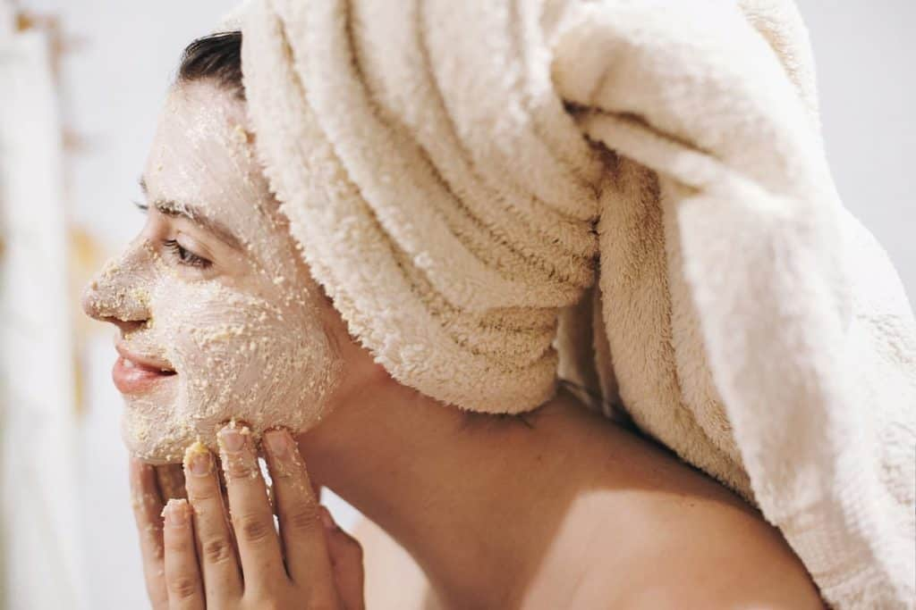 woman using a scrub on her face as example in post on best exfoliators for acne