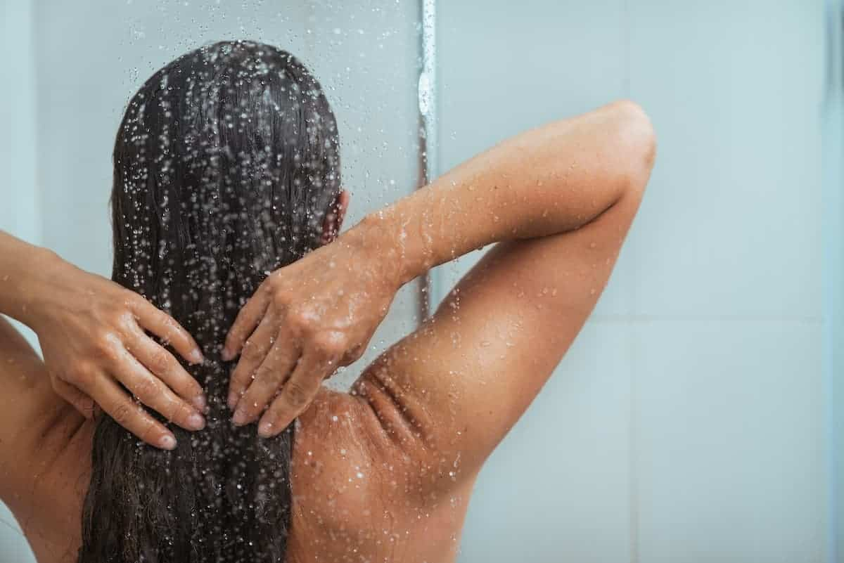 tan woman taking a shower after tanning