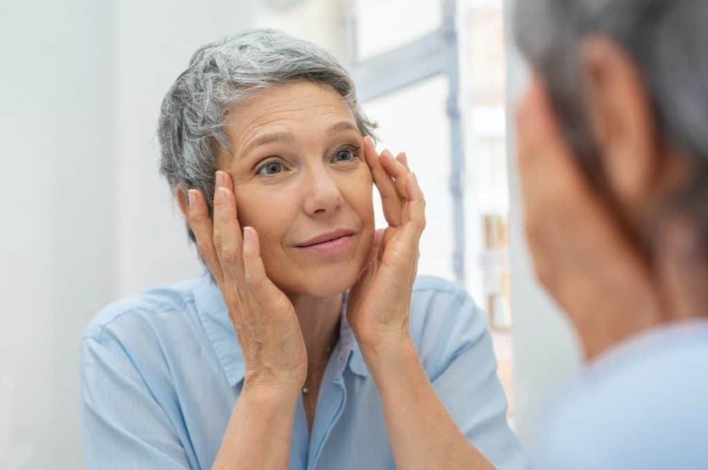 Older Woman looking in the mirror at her crepey skin