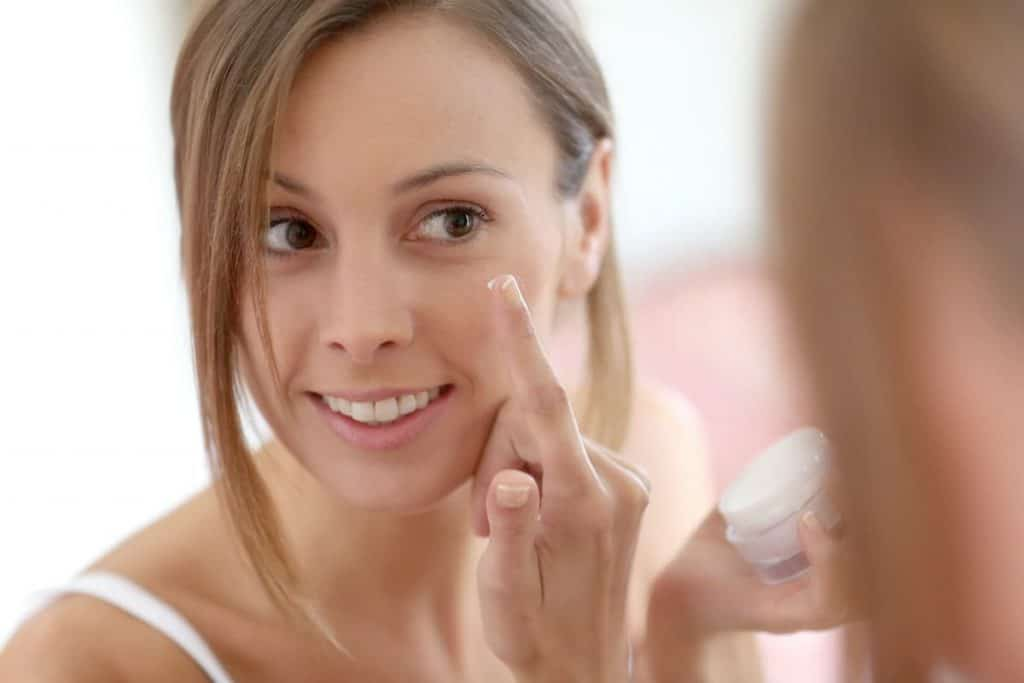 woman applying water based primer to her face